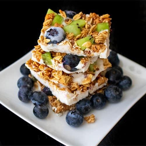 Granola bark realizado con granola Nutrisnacks, arándanos y kiwi, servido sobre plato blanco