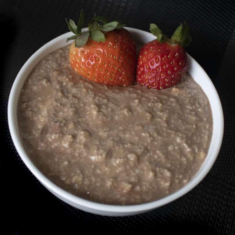 Overnight de avena integral con chocolate servido en un tazón con fresas frescas